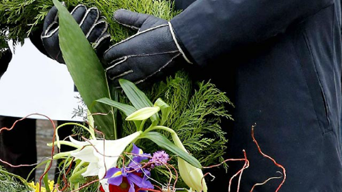 класть похоронный венок на могилу