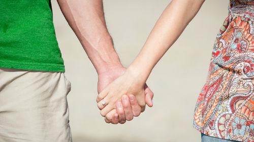 Мужчина держит руки женщины в своих
